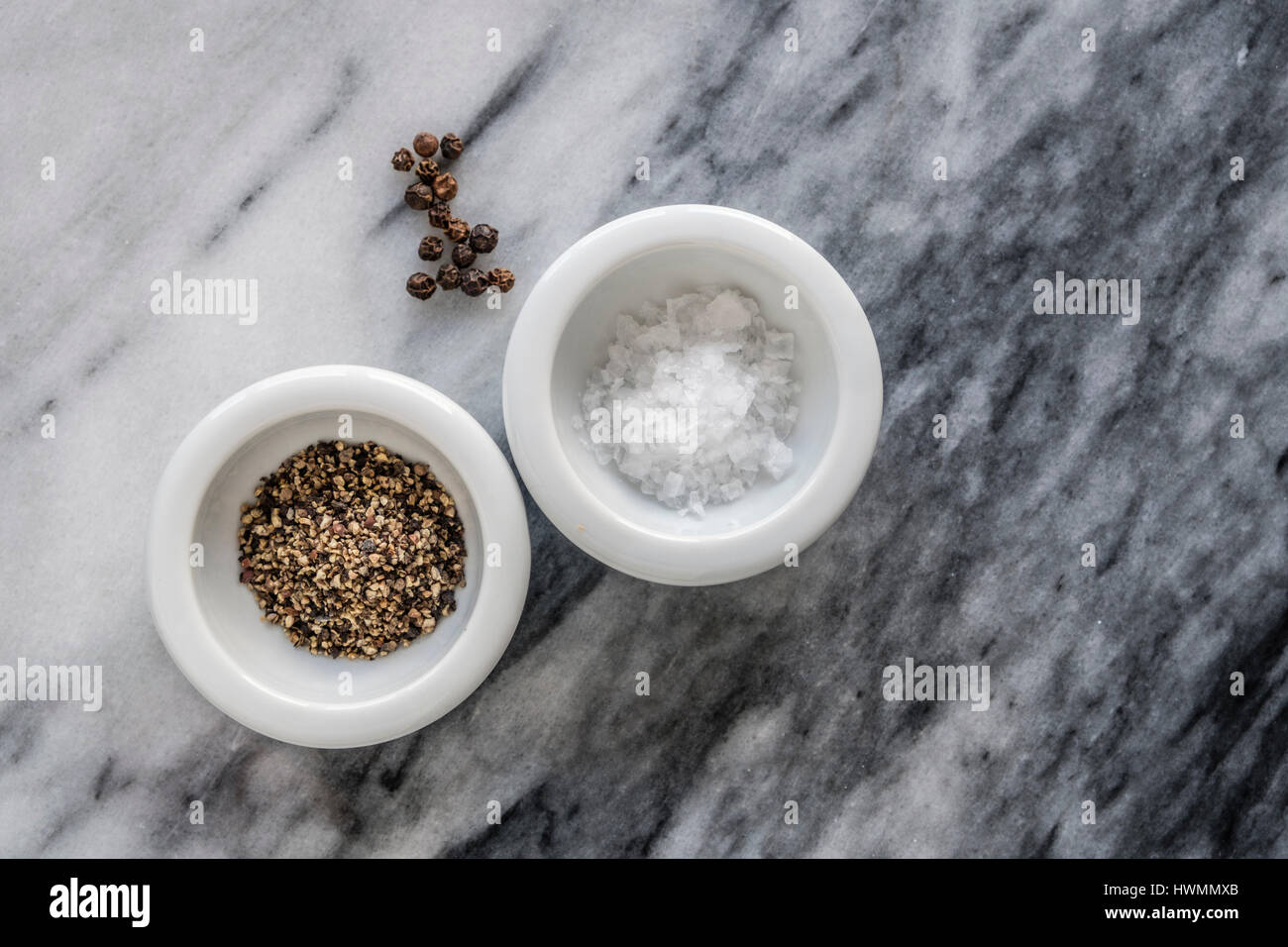 Two small white dishes of sea salt flakes and freshly ground black pepper and scattering of peppercorns. Top down - Stock Image