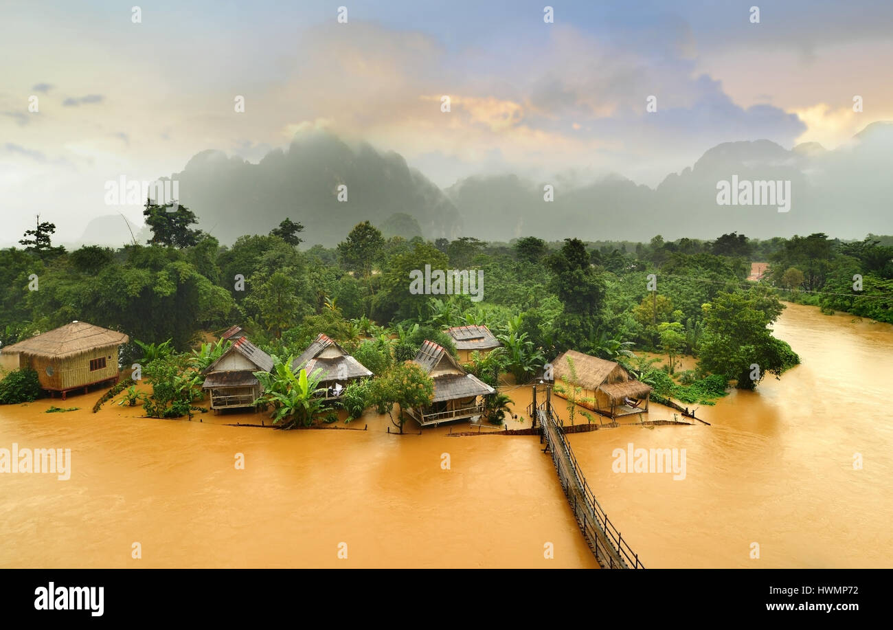 Vang Vieng Laos landmark the hut village with the wooden brigde in cloudy and morning low lighthing - Stock Image