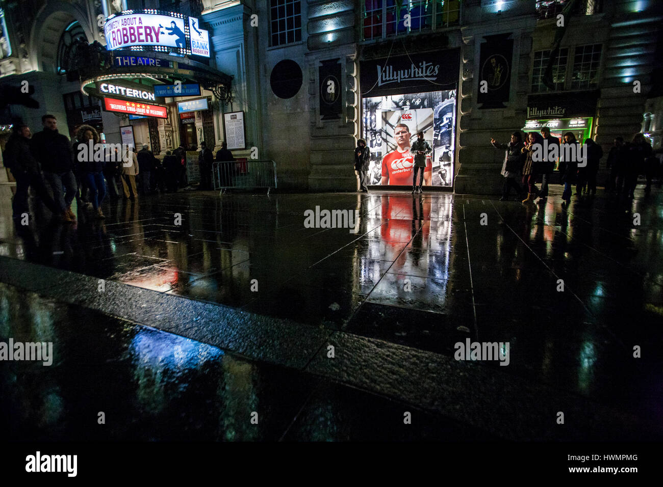 night view of people and reflections on wet street in piccadilly circus - Stock Image