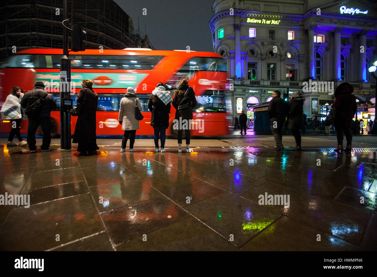 london routemaster bus in piccadilly circus people standing in the rain - Stock Image
