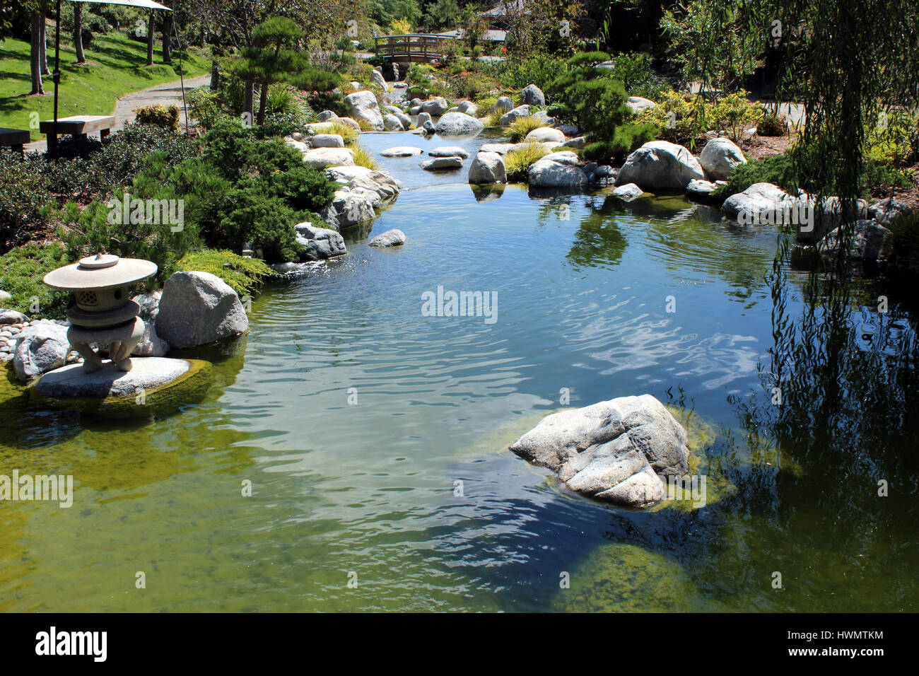 Beautiful Stream With Rocks And A Wooden Bridge In A Garden Setting