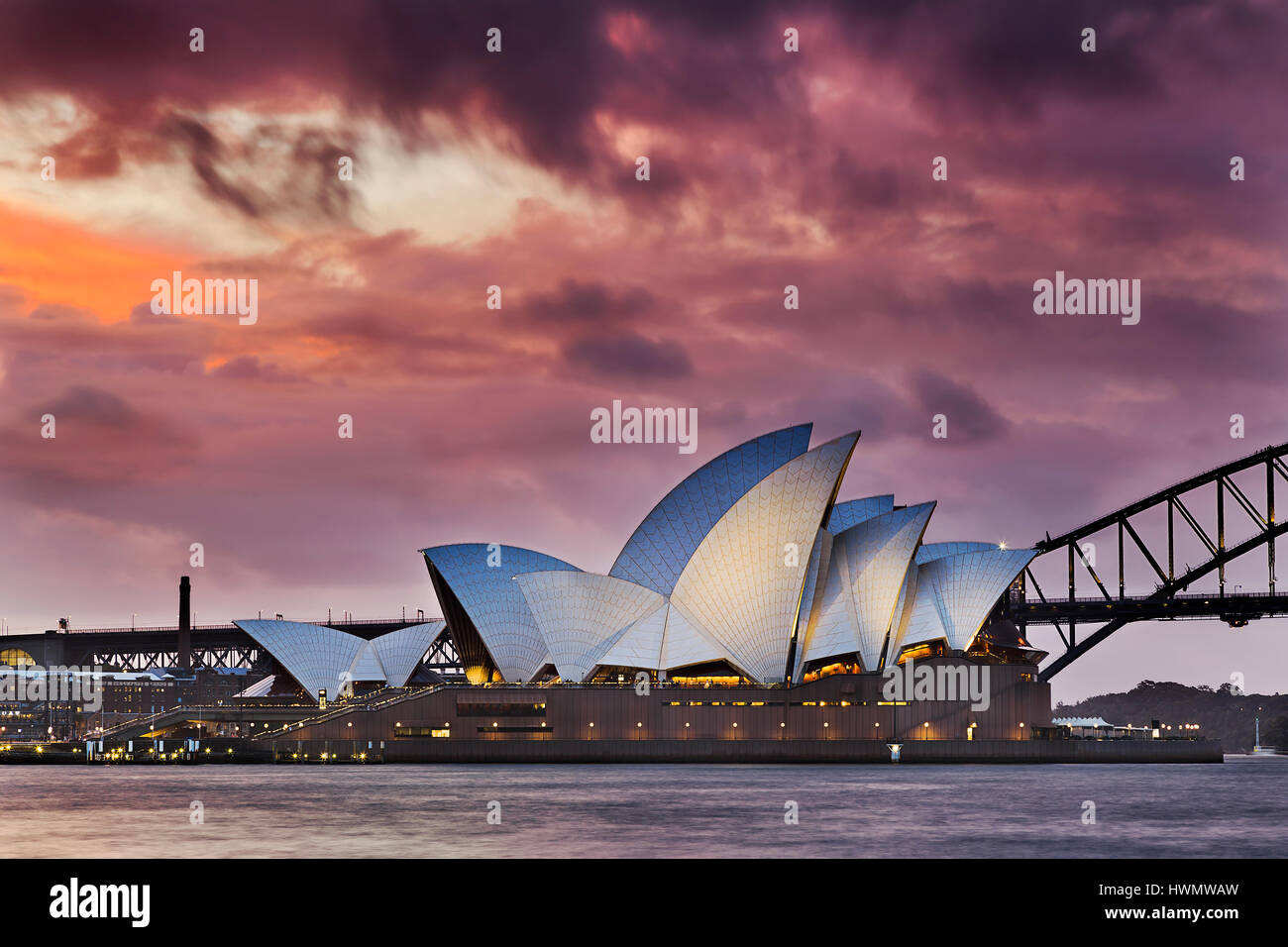 Sydney, Australia - 19 March 2017: Colourful sunset through thick clouds over world famous landmark - Sydney Opera - Stock Image