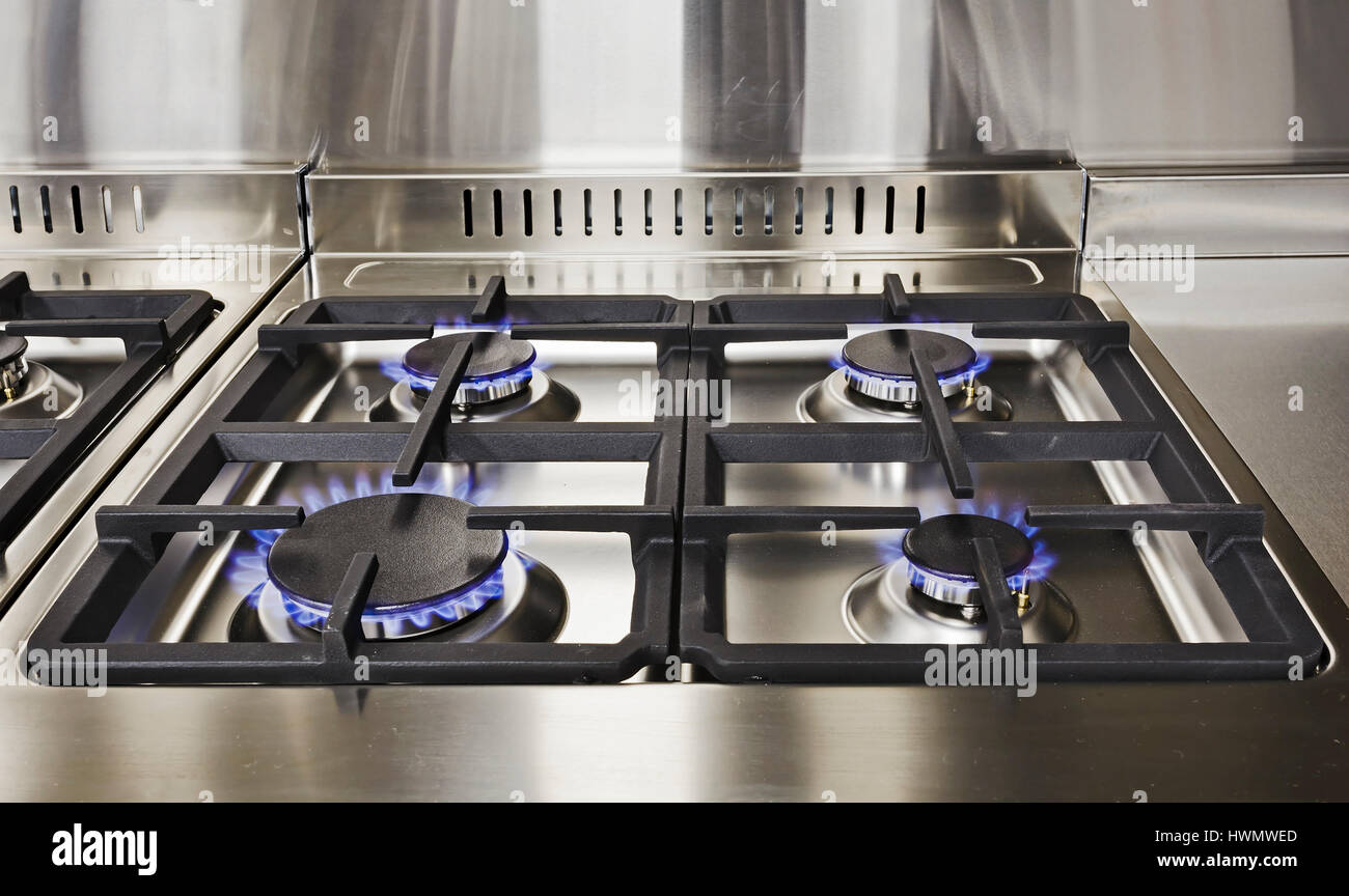 Burning blue flames of gas on cooktop under grills in a modern clean kitchen. Modern household appliance - Stock Image