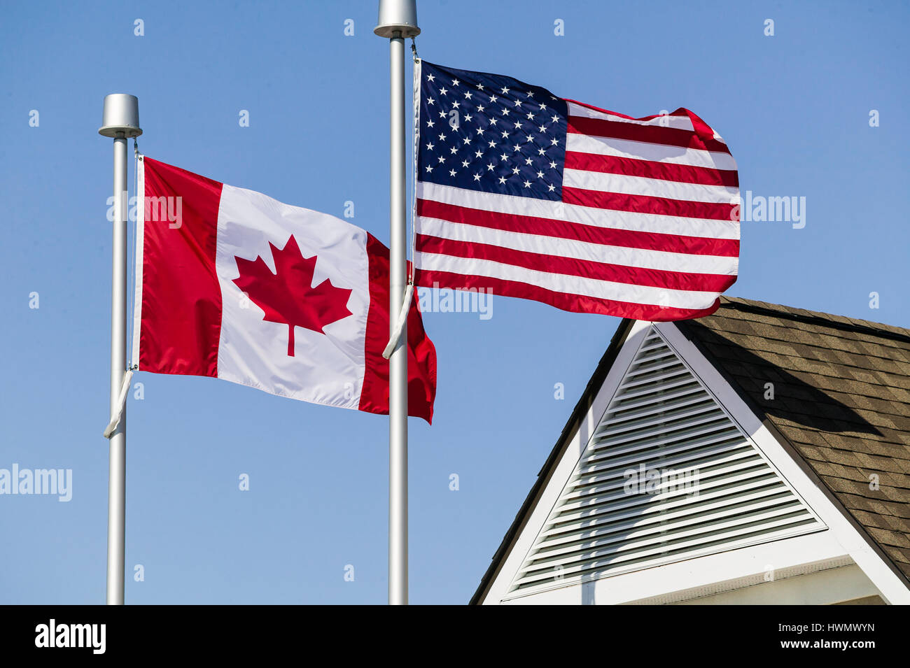 150546353ad Stock Photo. Enlarge. An American flag and a Canadian flag flying side by  side.