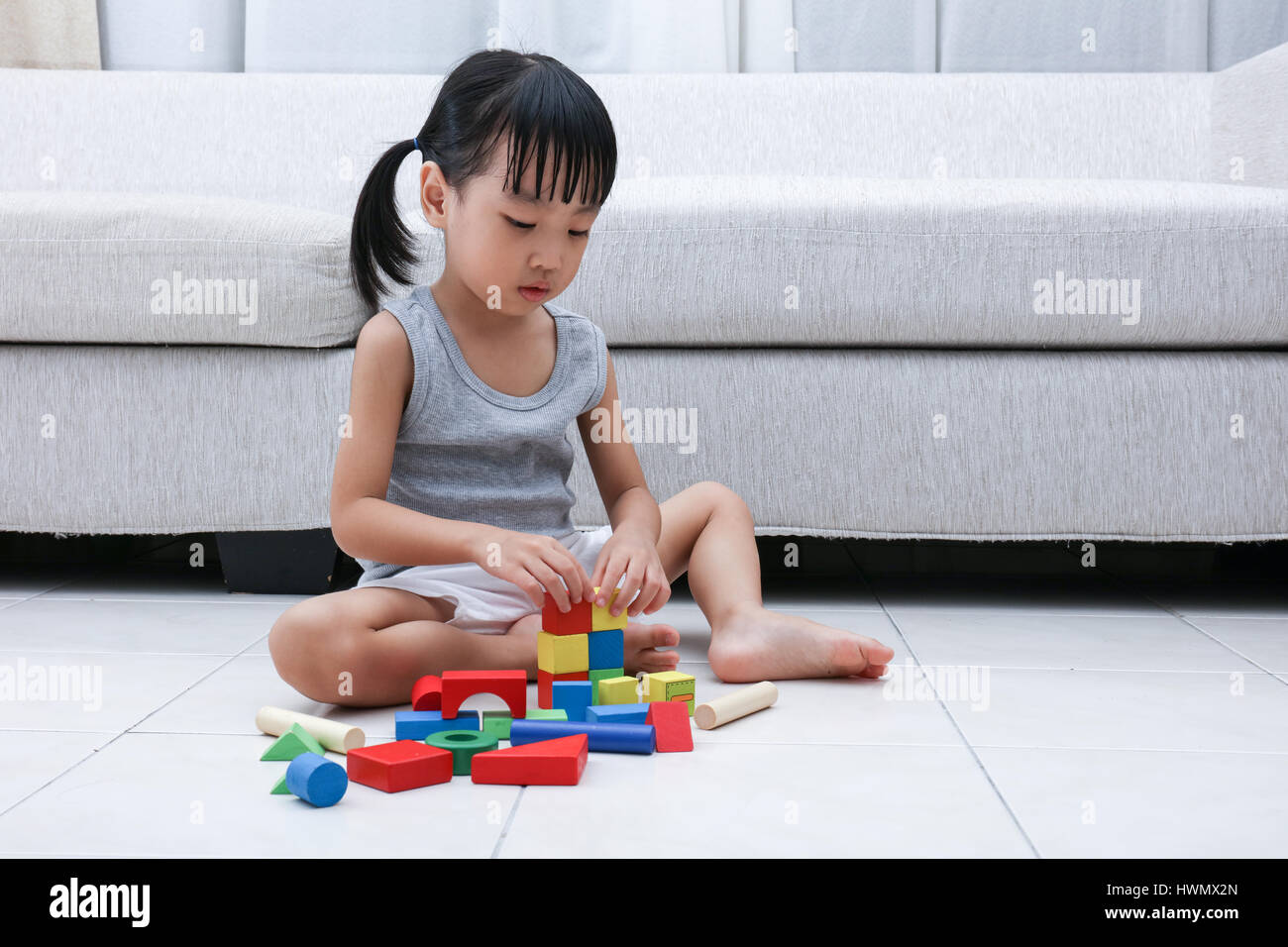 Asian Chinese little girl playing blocks on the floor in the living room at home. Stock Photo