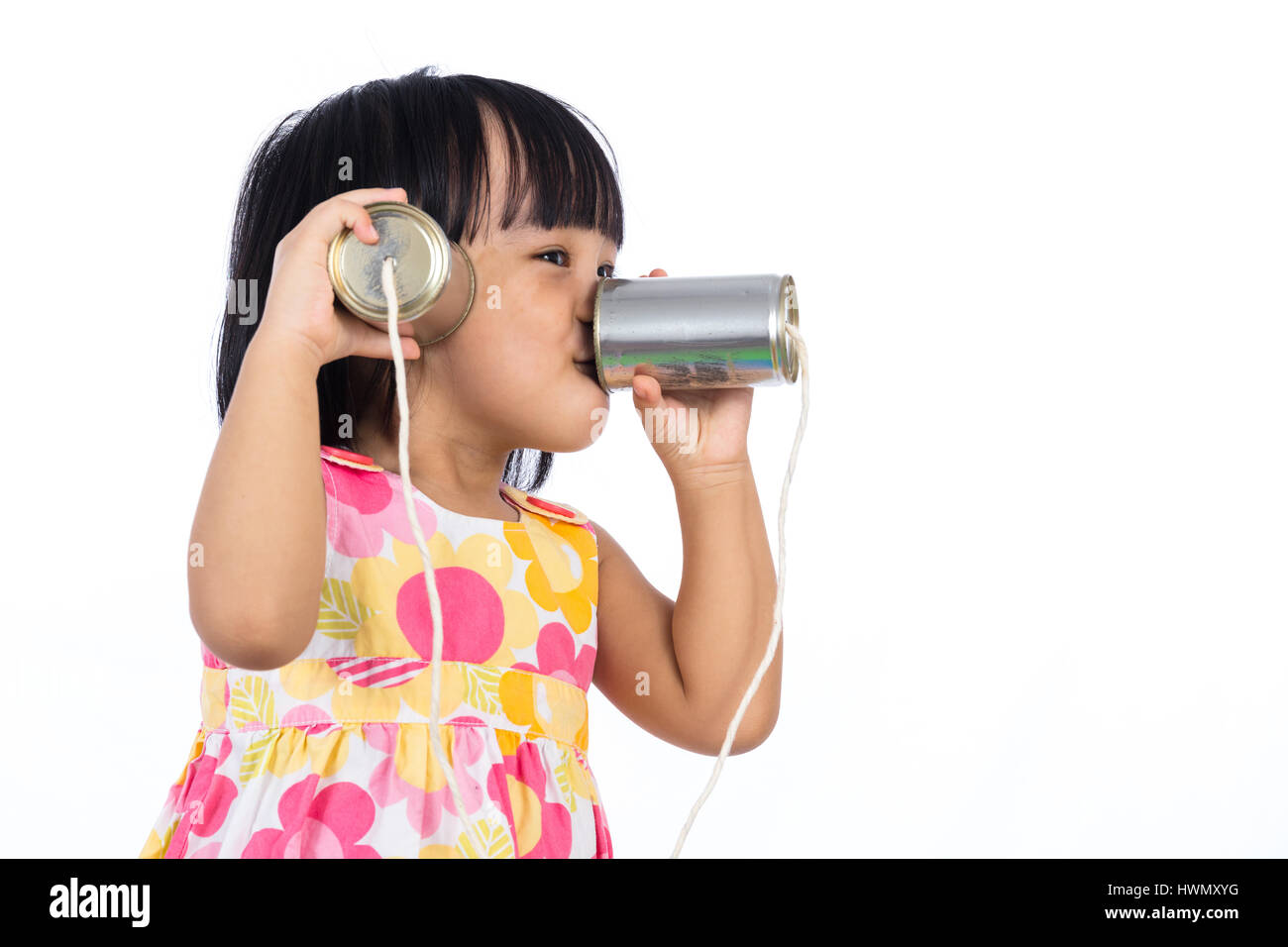 Asian Chinese little girl playing tin can phone in isolated white background. - Stock Image