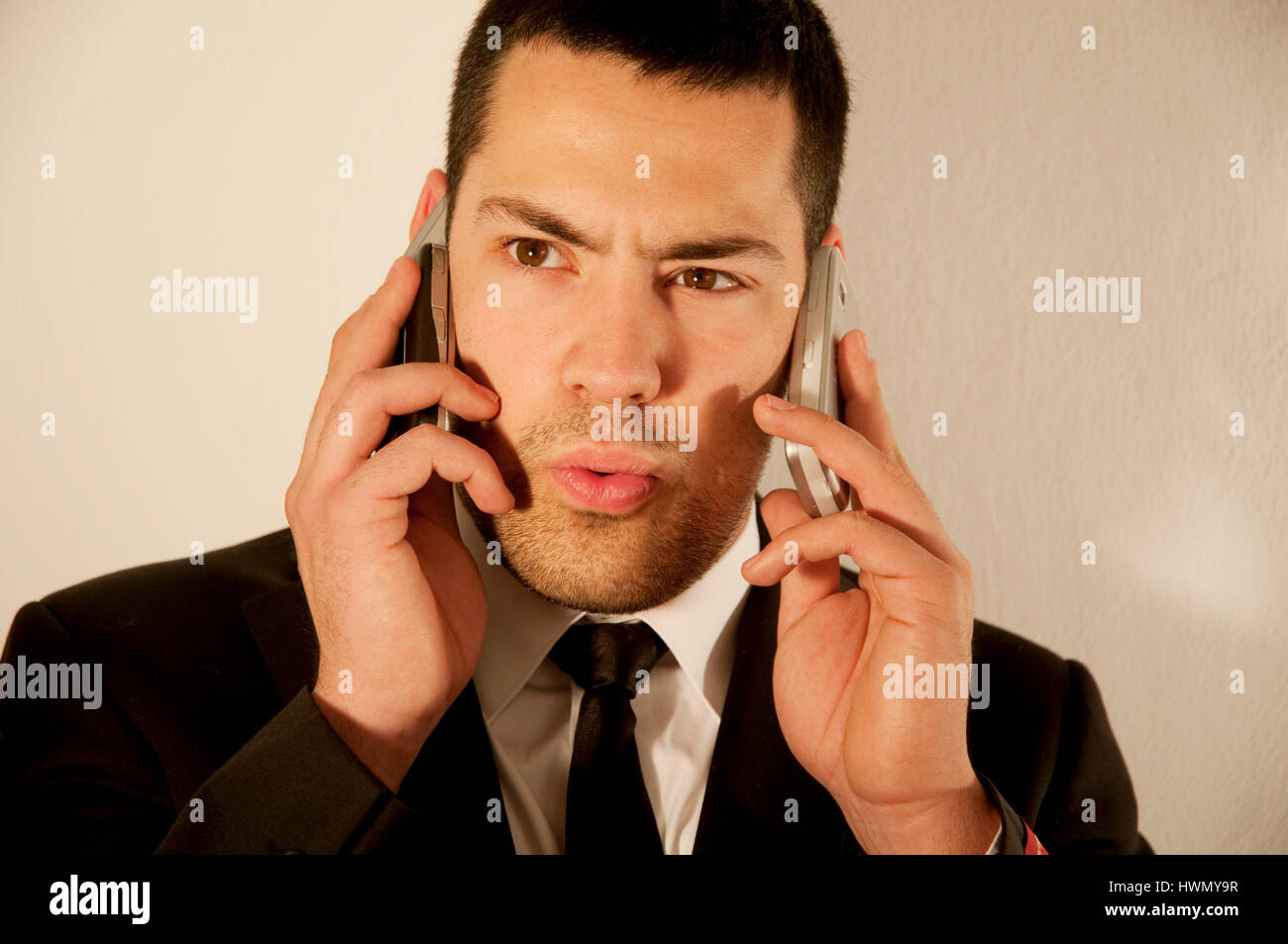 Business man using two mobile phones. - Stock Image
