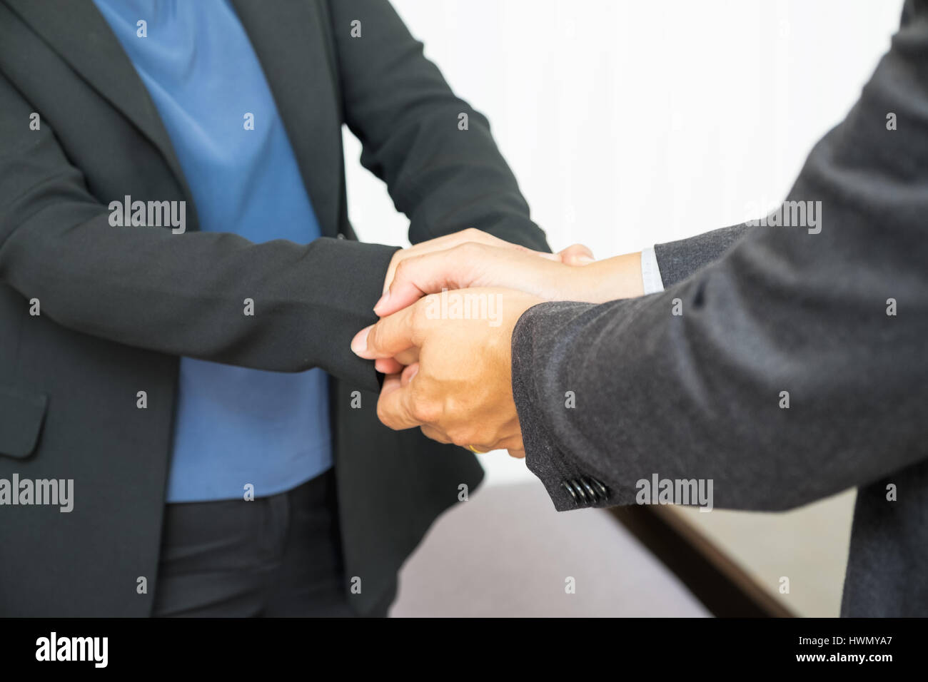 Close up businessman use two hand holding businesswoman hand for Congratulations about success of plan. - Stock Image