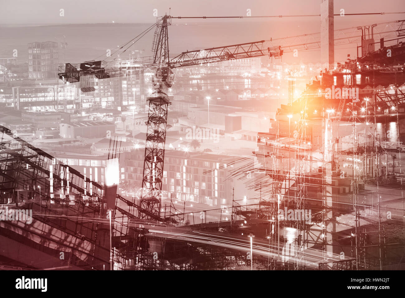 Work in progress in the city against illuminated buildings in city - Stock Image