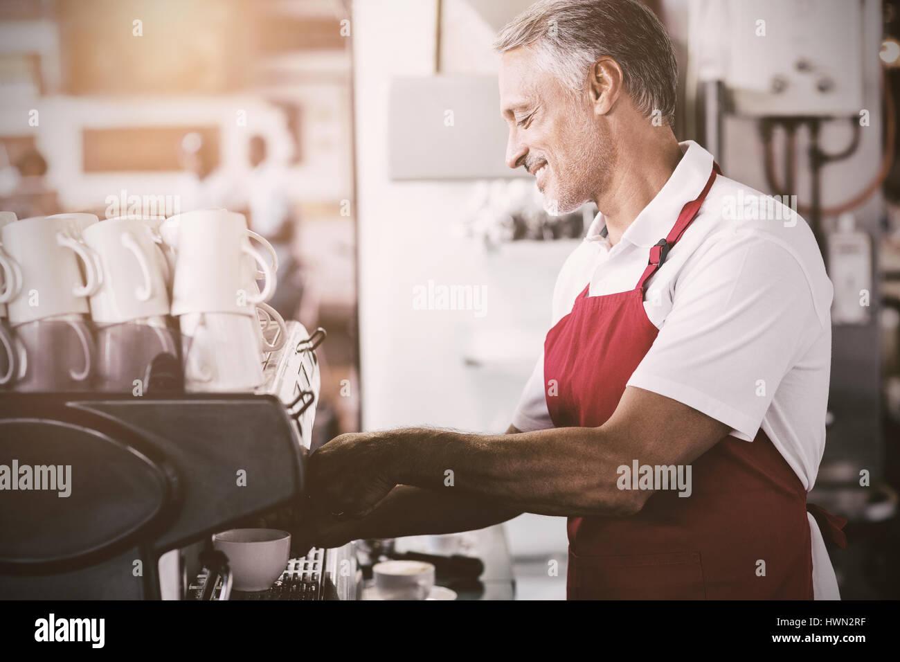 flare against happy barista using coffee machine - Stock Image