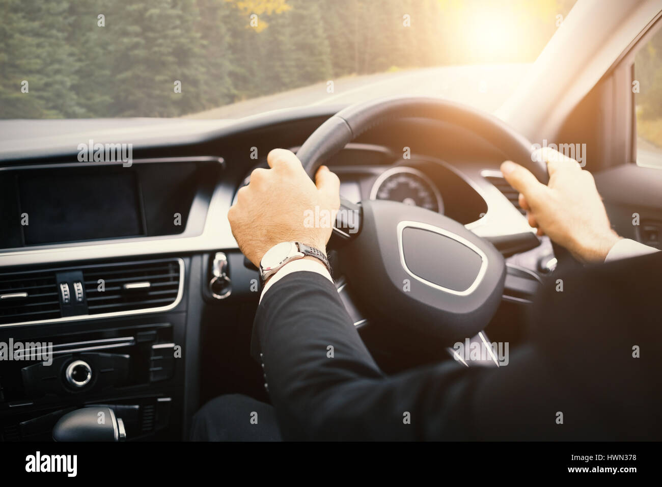 Businessman in the drivers seat in his car - Stock Image