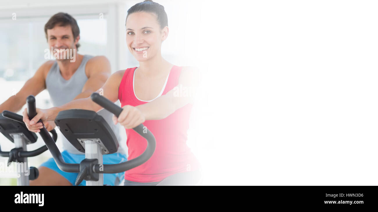 Smiling young couple working out at spinning class in a bright gym - Stock Image