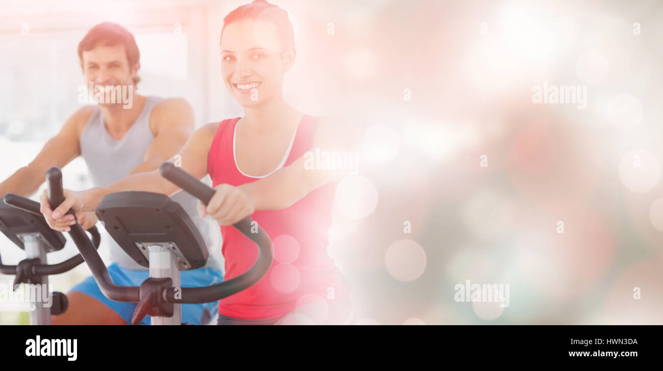 Smiling young couple working out at spinning class in a bright gym Stock Photo