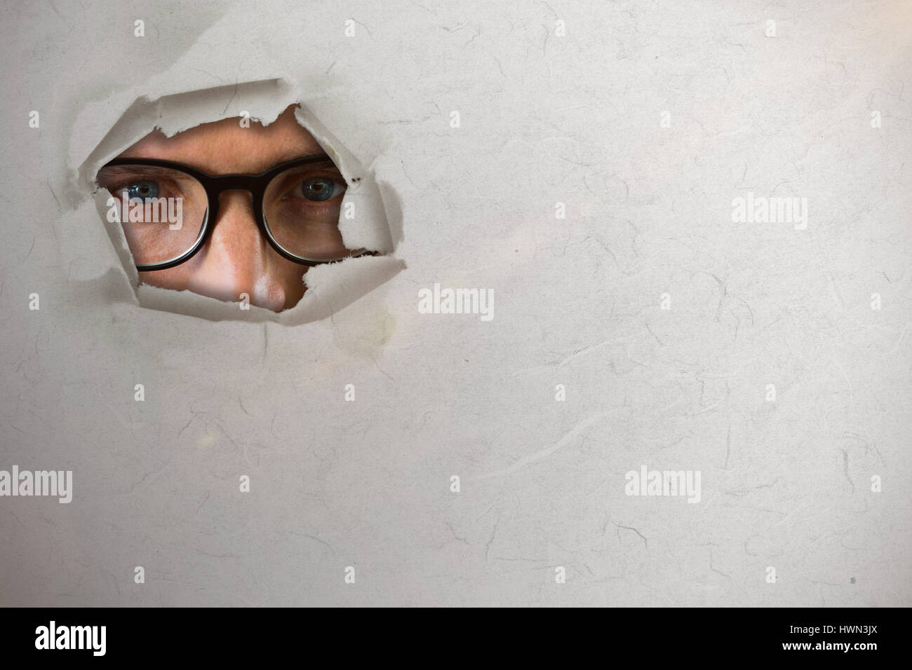 Close up portrait of man wearing eyesglasses against circle hole in paper 3d - Stock Image