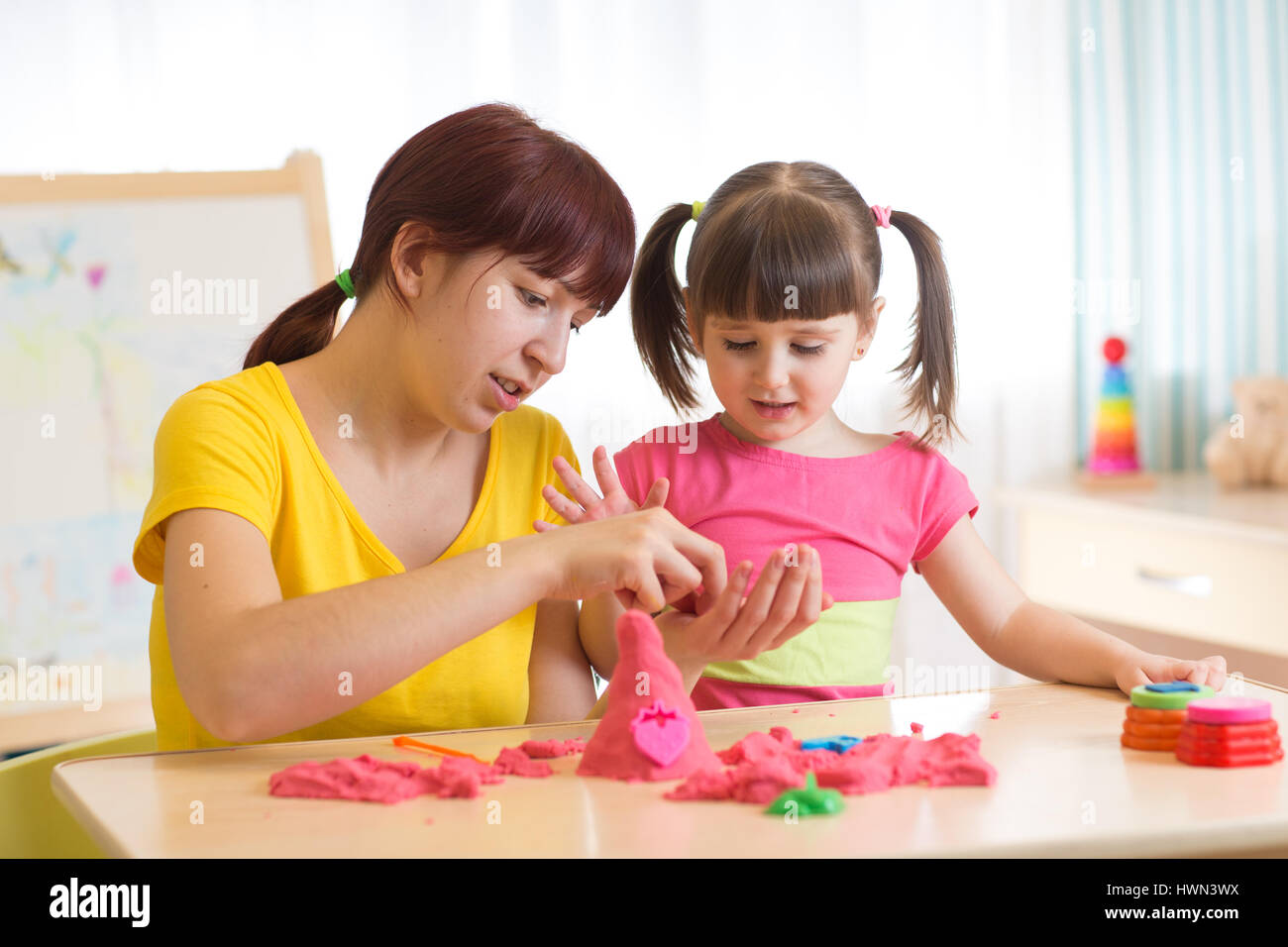 Child girl and mother playing with kinetic sand at home - Stock Image
