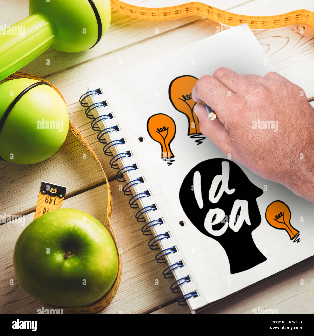 Cropped image of hand holding a pencil against notepad with indicators of healthy lifestyle - Stock Image