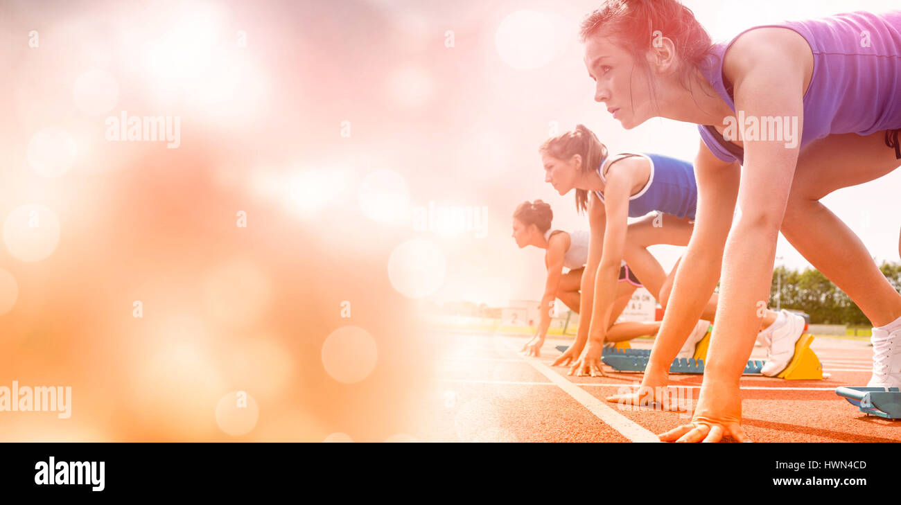 Side view of women on starting line of track field - Stock Image