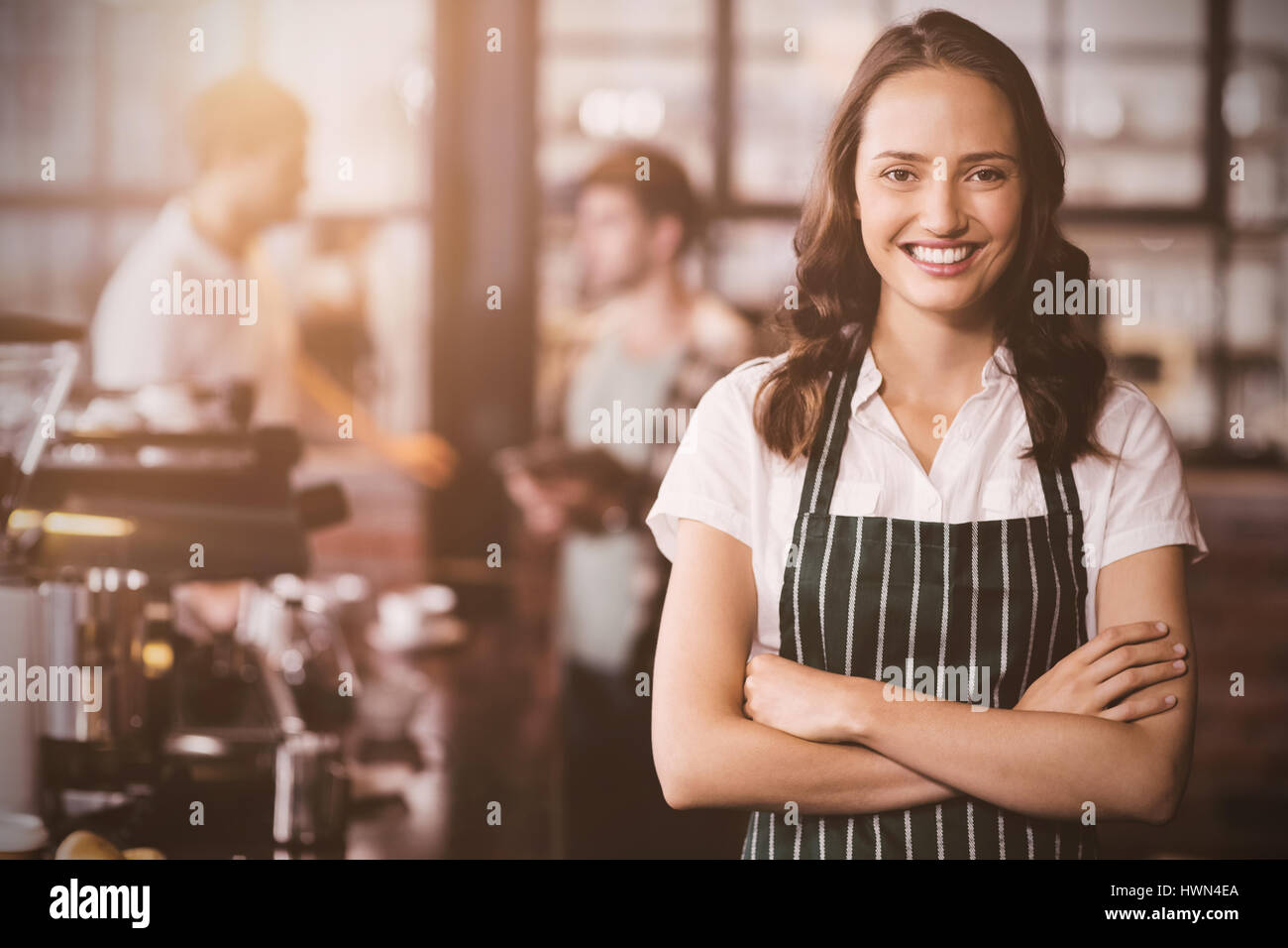 flare against pretty barista with arms crossed - Stock Image