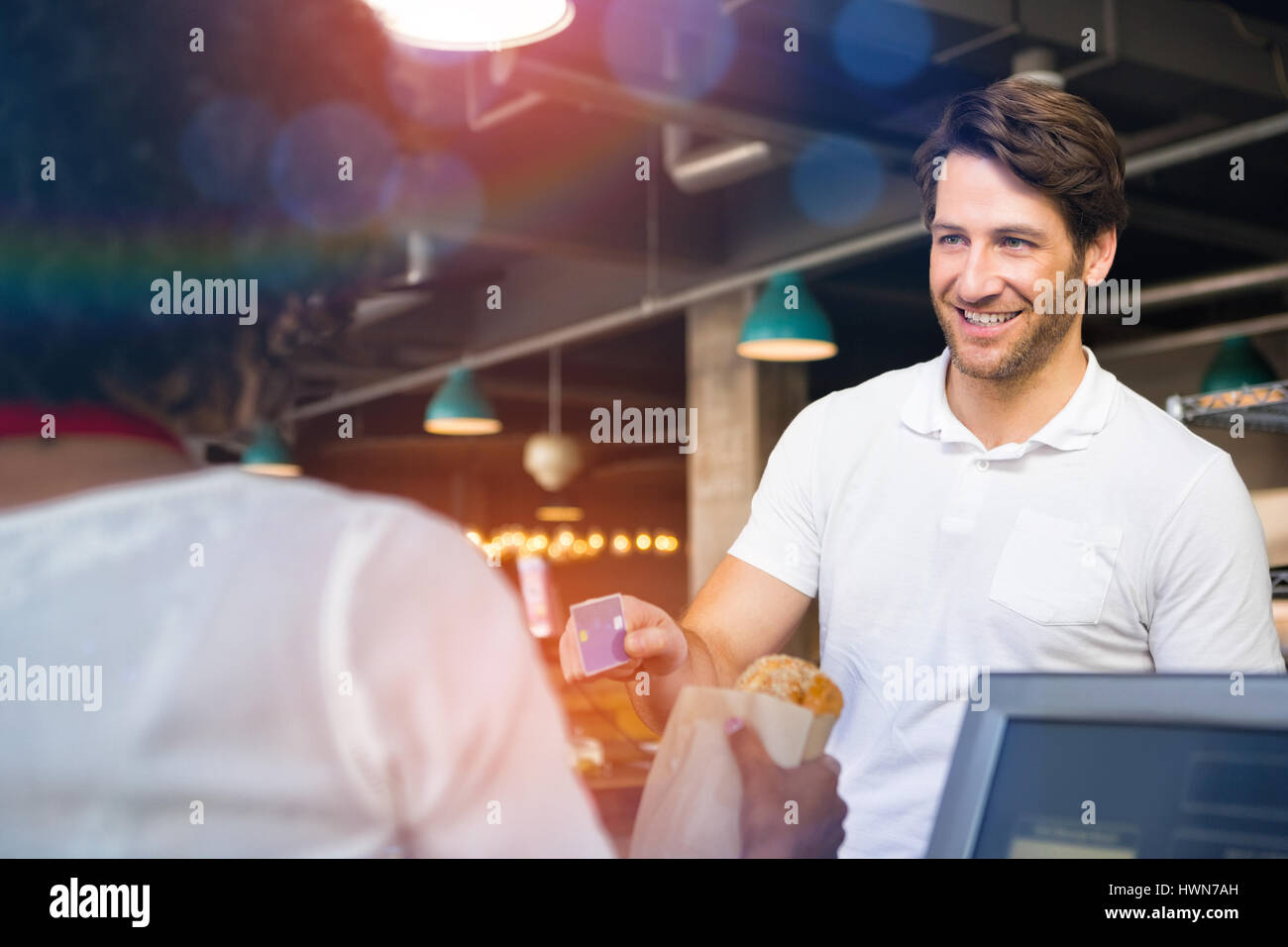 Graphic image of flare against happy customer paying by credit card for bread - Stock Image