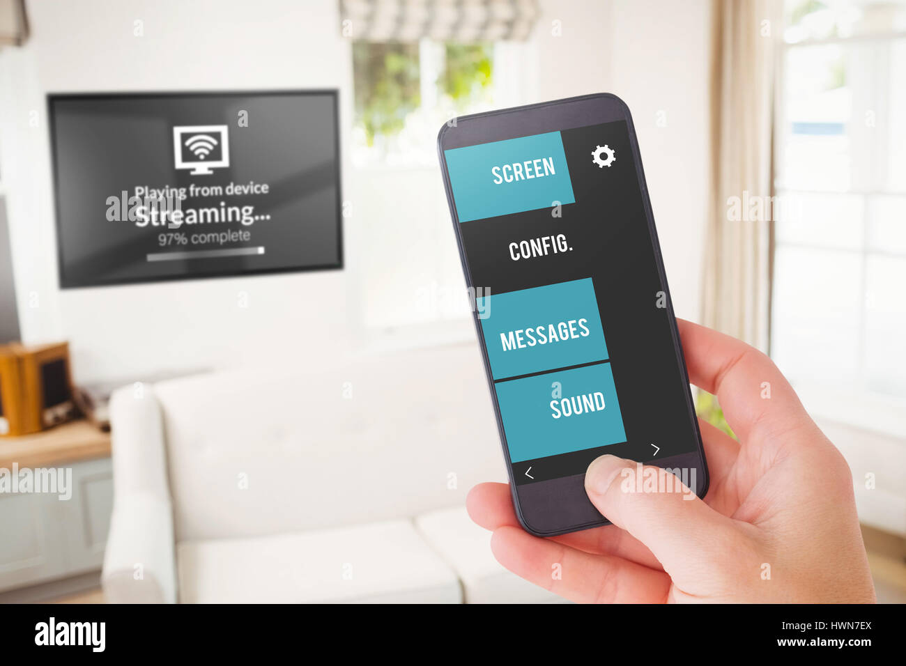 Female hand holding a smartphone against sitting room Stock Photo
