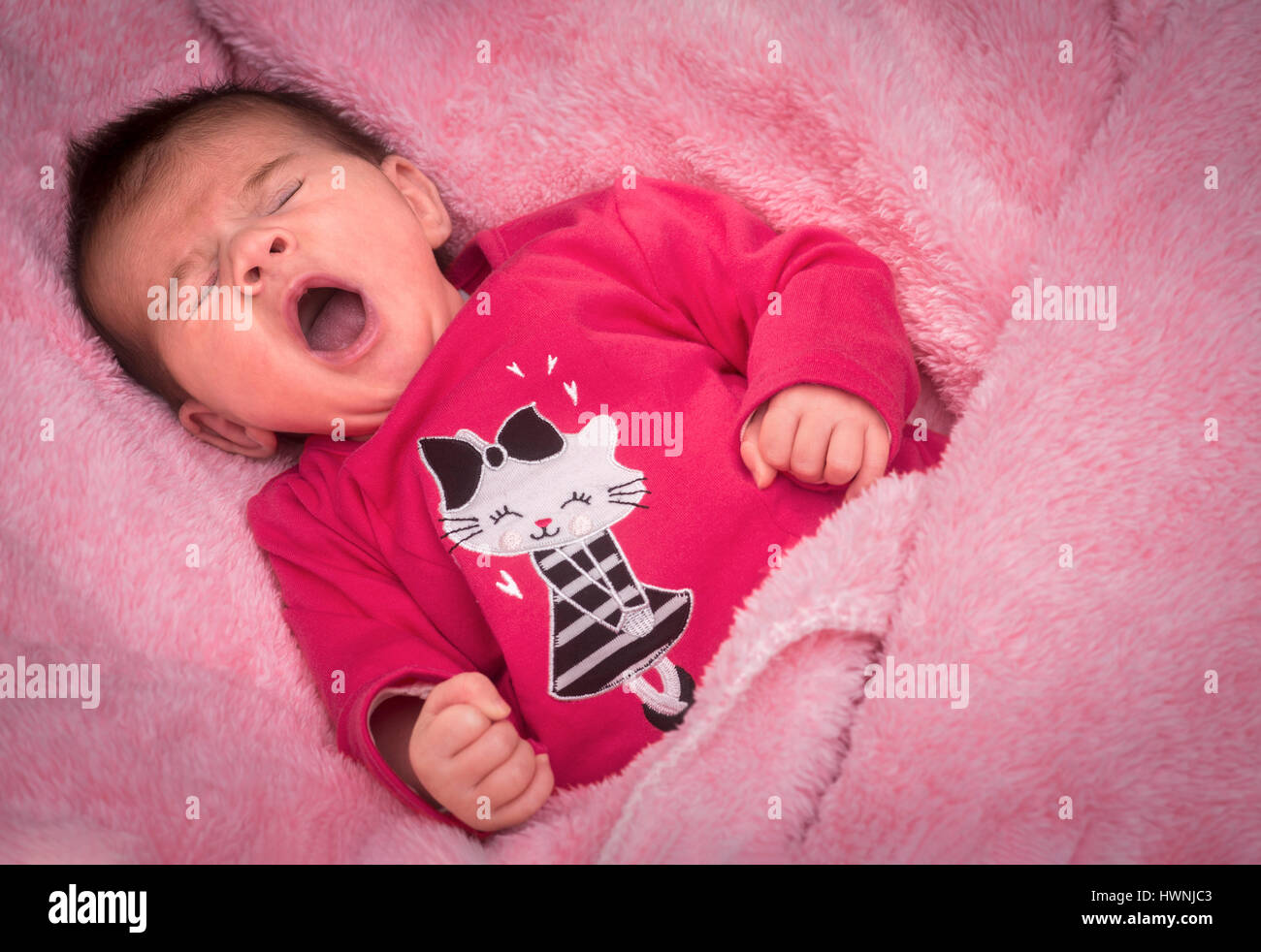 A newborn baby girl yawning on a pink blanket, certainly gazed lovingly by her parents who take advantage of the - Stock Image