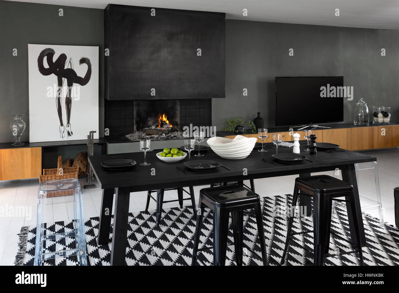 A laid out contemporary table - made out of a charred wood (shou-sugi-ban technique) - in a modern interior with - Stock Image