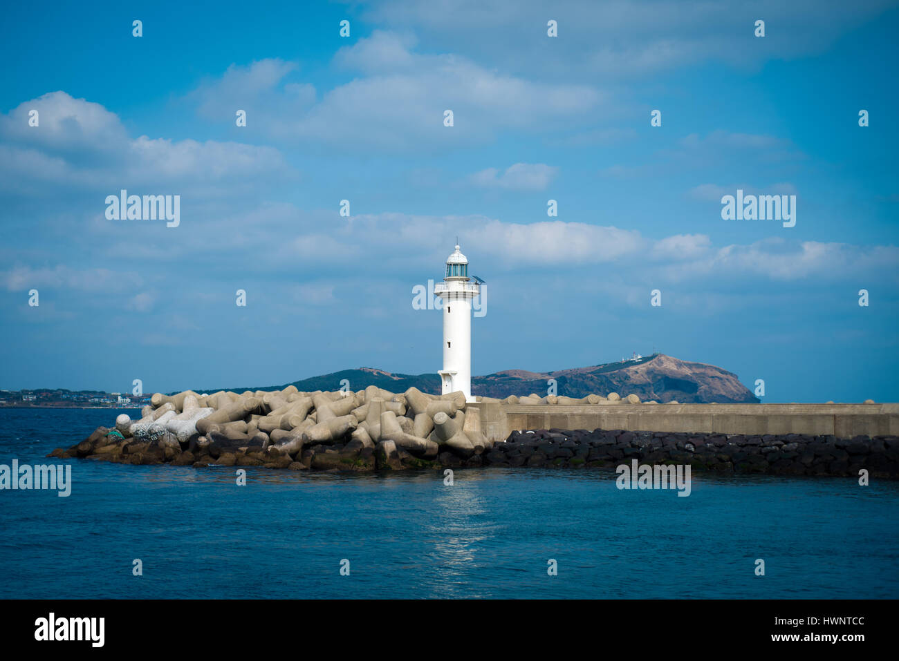 White Lighthouse Against A Blue Sky - Stock Photo