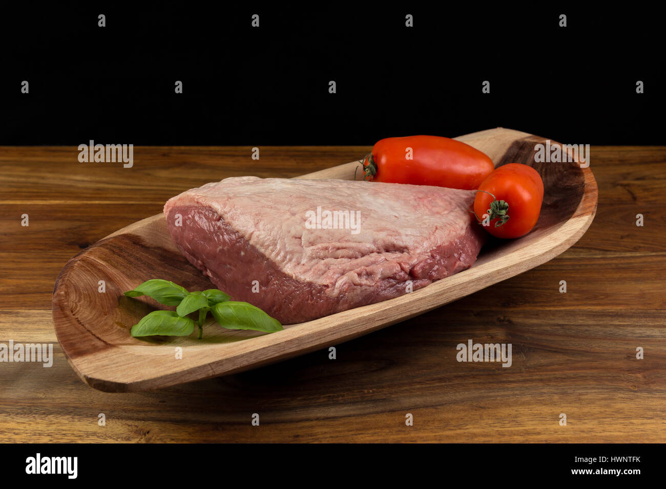 Full piece of raw cow beef (picanha), tomatoes and basil on a wood rectangular bow and natural wood table - black - Stock Image
