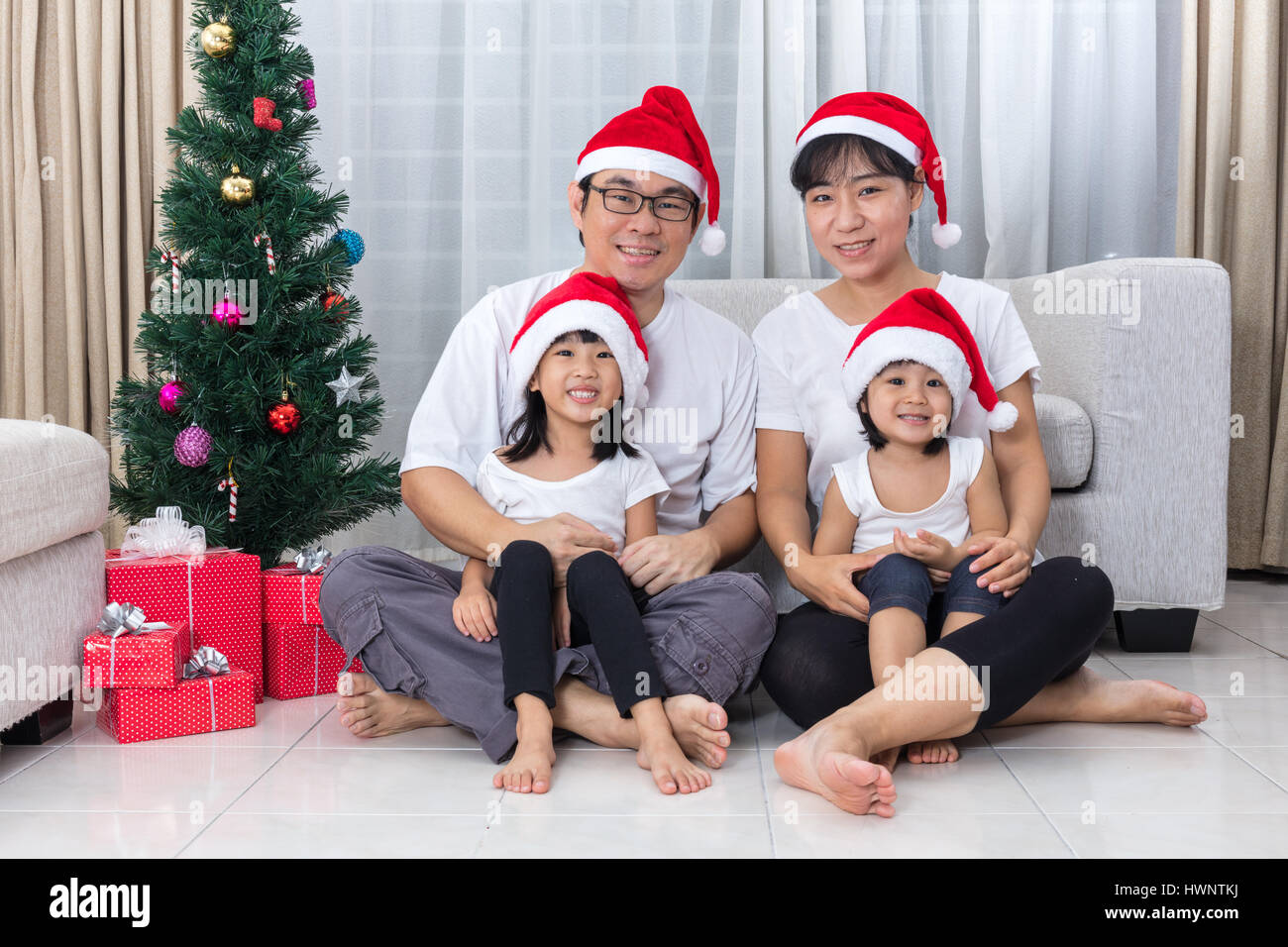 23f6176d4b001 Happy Asian Chinese family sitting on the floor celebrating Christmas in  the living room at home with Santa Claus Hat.