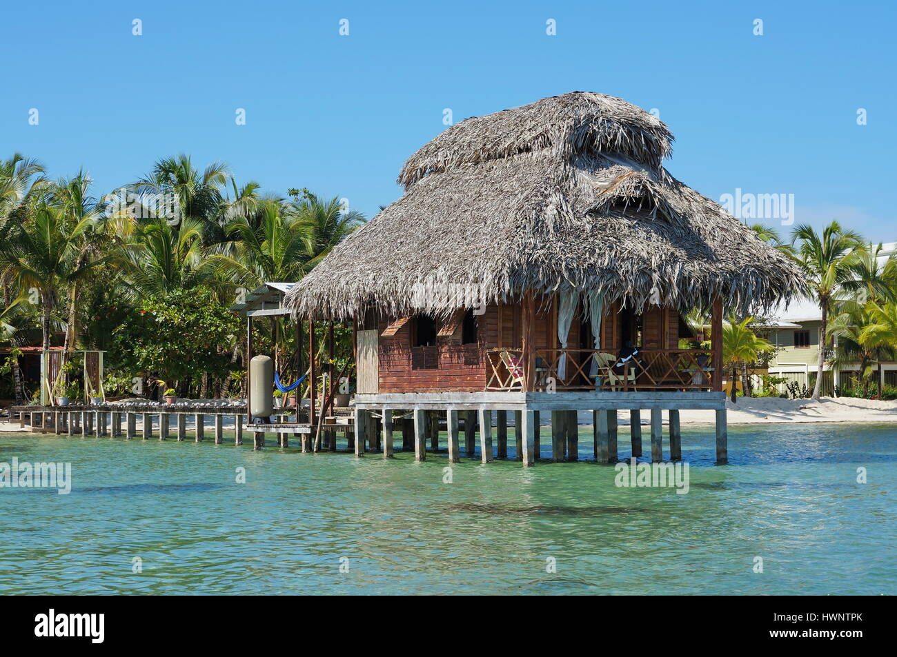 Overwater bungalow with thatch roof, Bastimentos island, Bocas del Toro, Caribbean, Panama - Stock Image