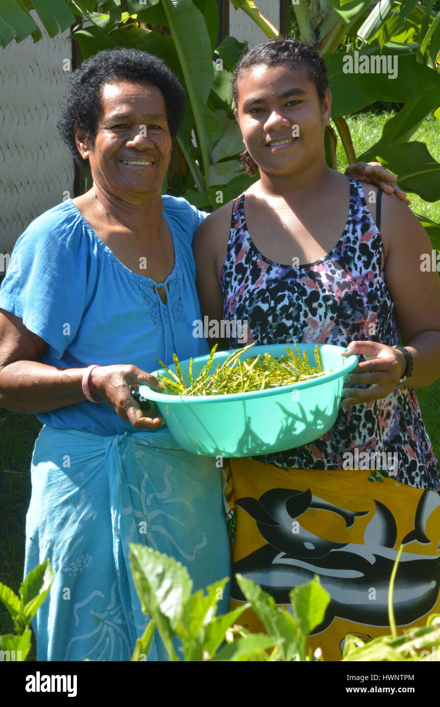 Indigenous Fijian mother and daughter collect together vegetables in the home garden. Stock Photo