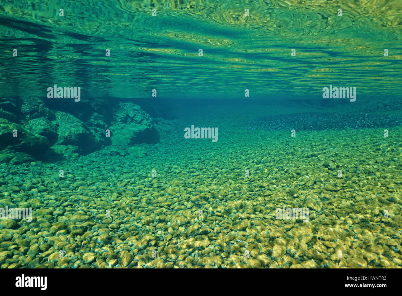 River underwater surface with pebbles on the riverbed, natural scene, Dumbea, New Caledonia, south Pacific - Stock Image