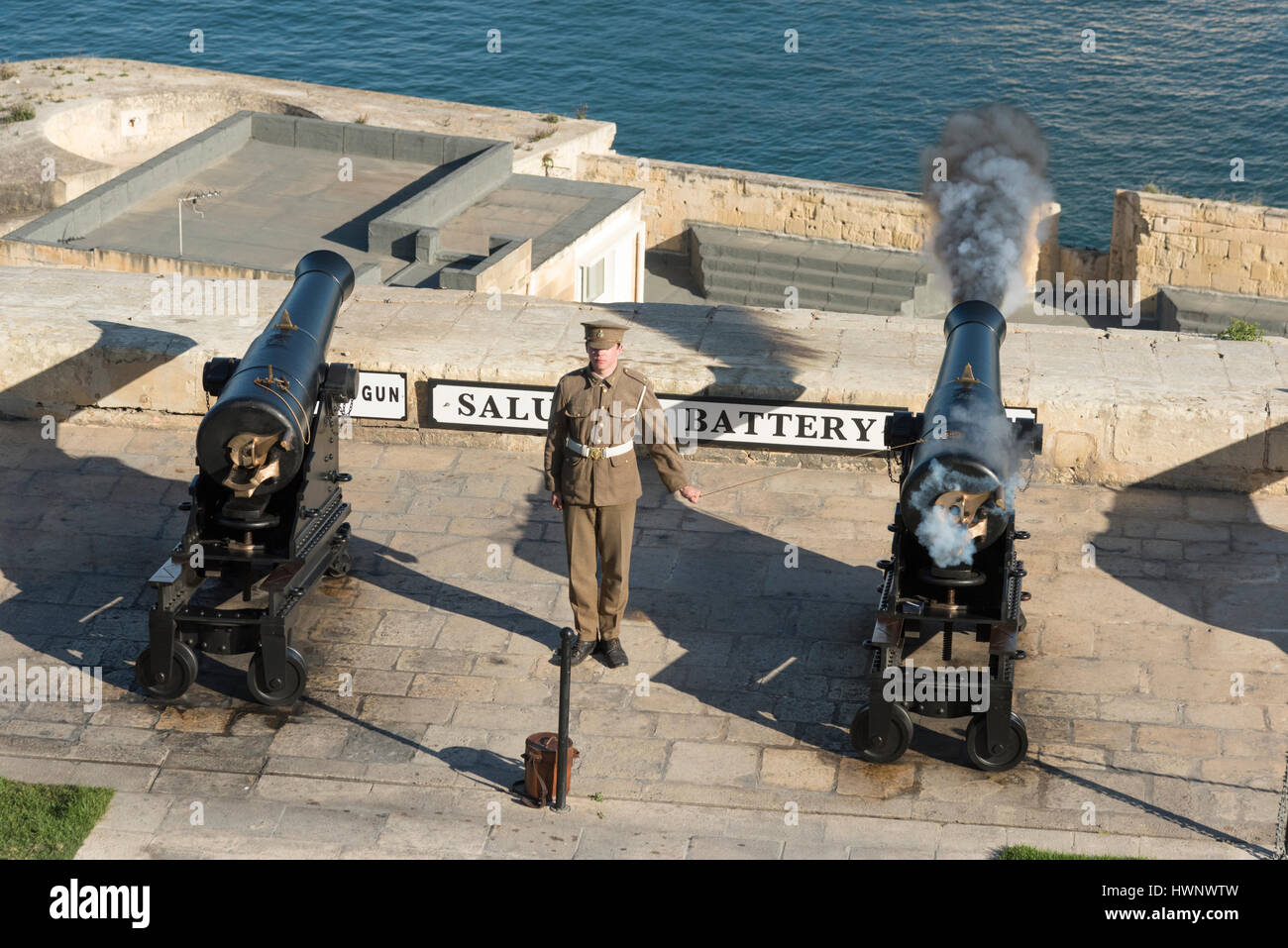 A soldier in uniform firing a canon at the saluting battery at Valetta Malta overlookingthe Grand Harbour for the - Stock Image