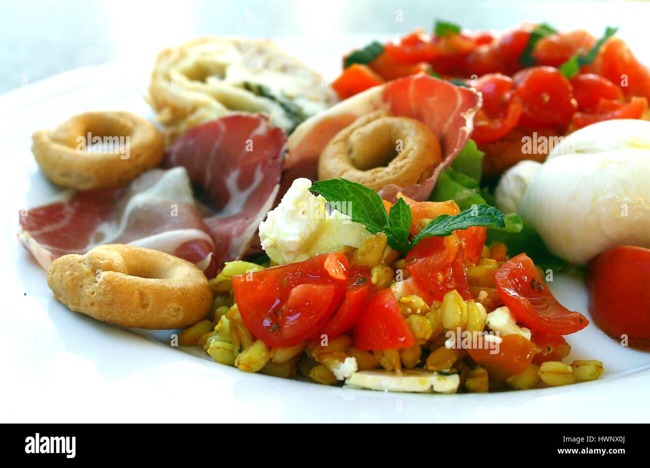 South Italy delicatessen with mozzarella cheese, tomato bruschetta, cold cuts - Stock Image