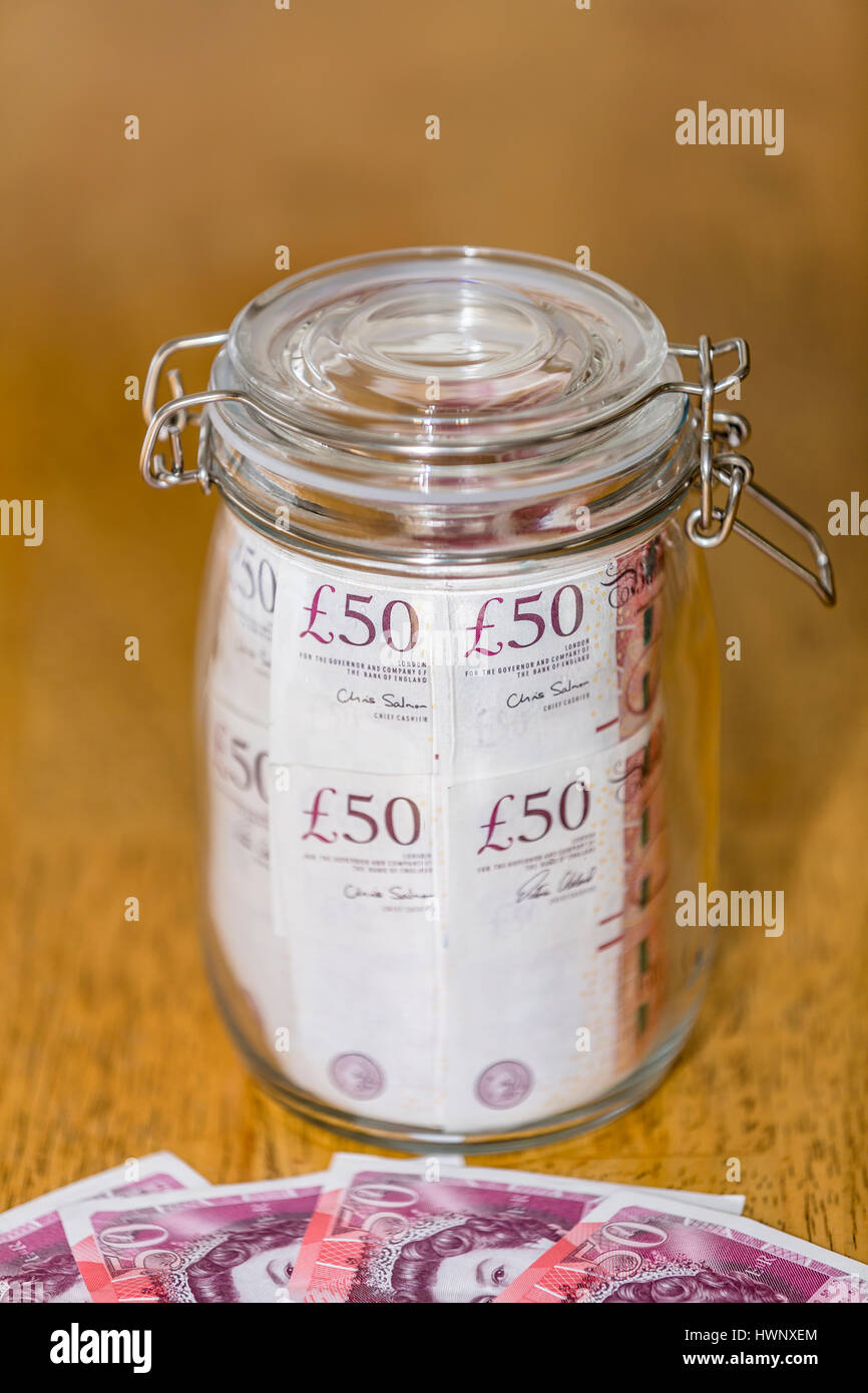 A jar full of £50 notes - Stock Image