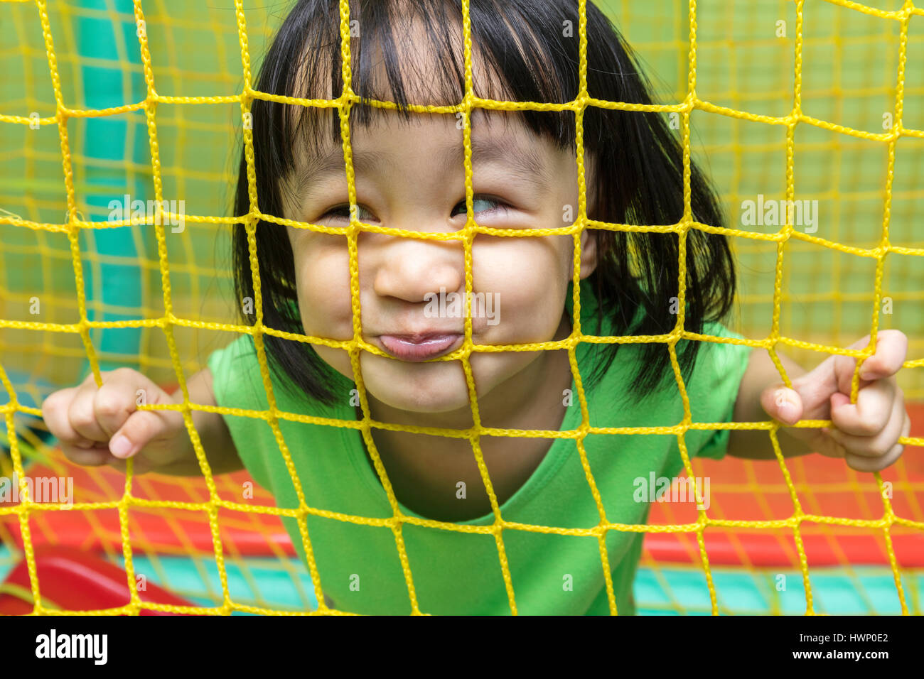 Happy Asian Chinese little girl playing behind the net at indoor playground. - Stock Image