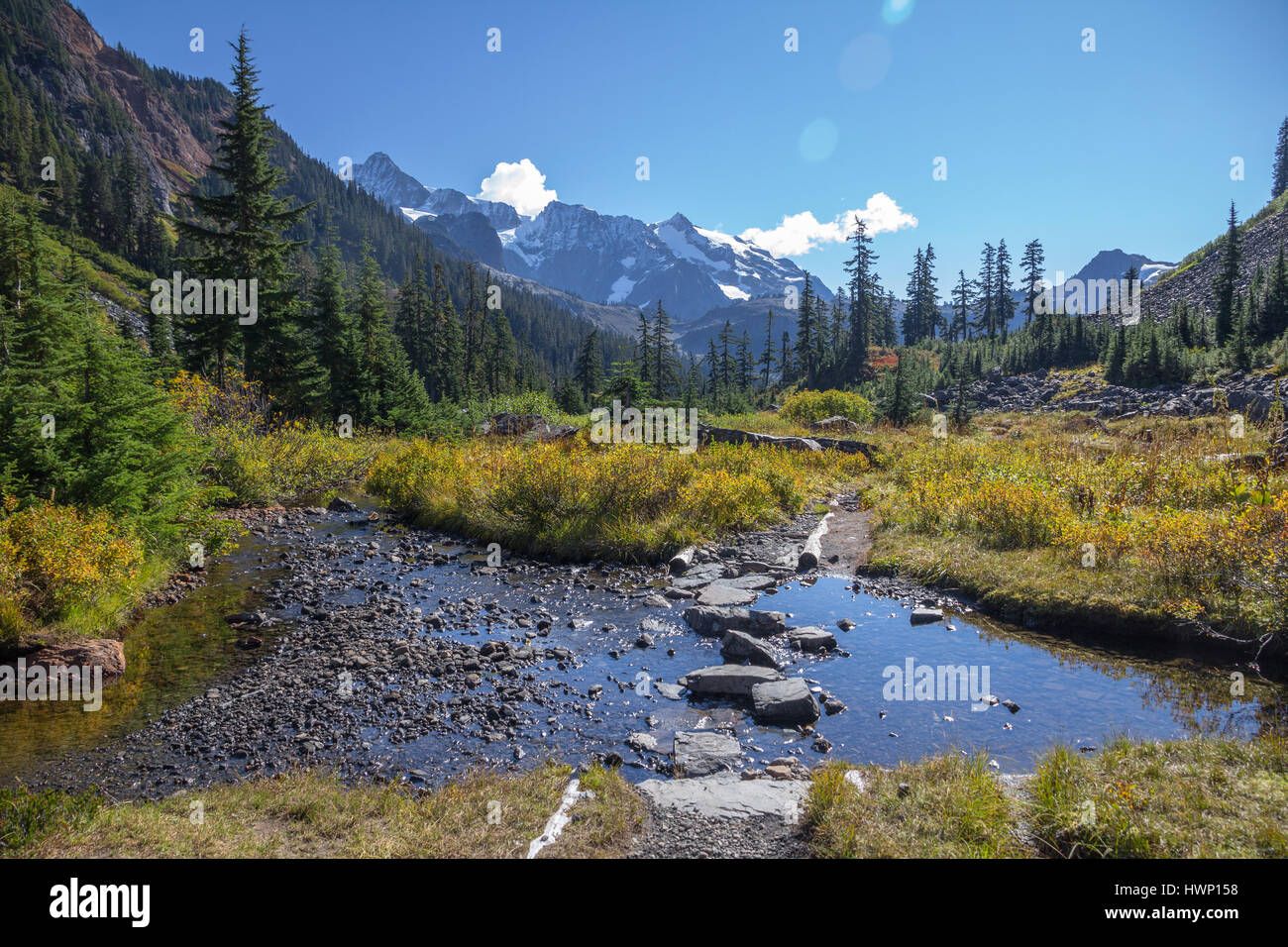 Shallow stream with stepping stones lies across the popular Lake Ann hiking trail near Mount Baker, WA Stock Photo