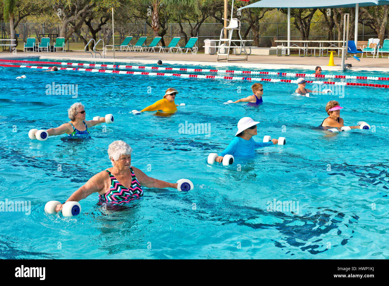 Group of women (various ages) attending Water Aerobics Class, working with 'water dumbbells'. - Stock Image