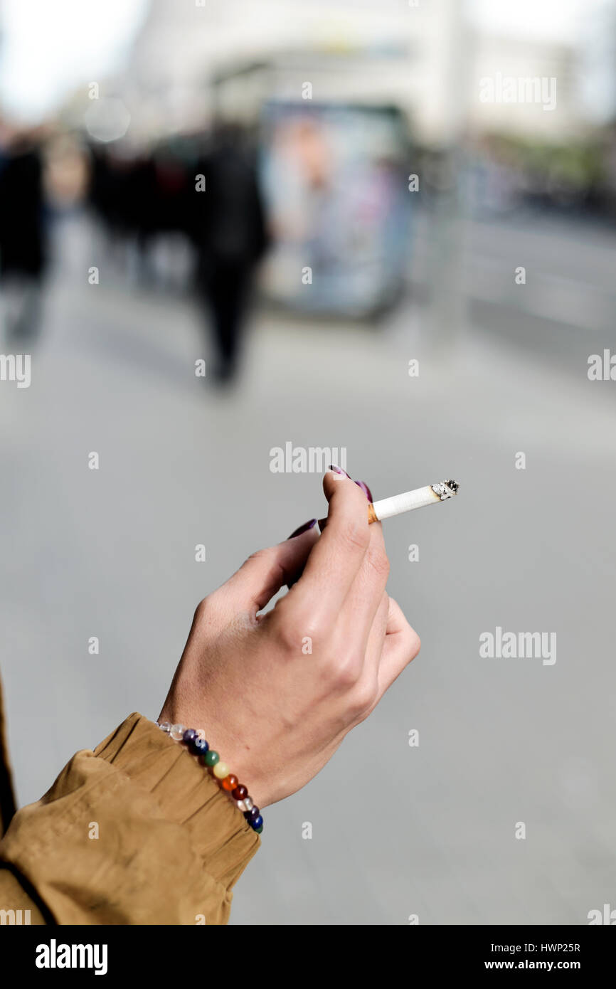 closeup of a young caucasian woman with purple nail polish in her fingernails smoking a cigarette in the street - Stock Image