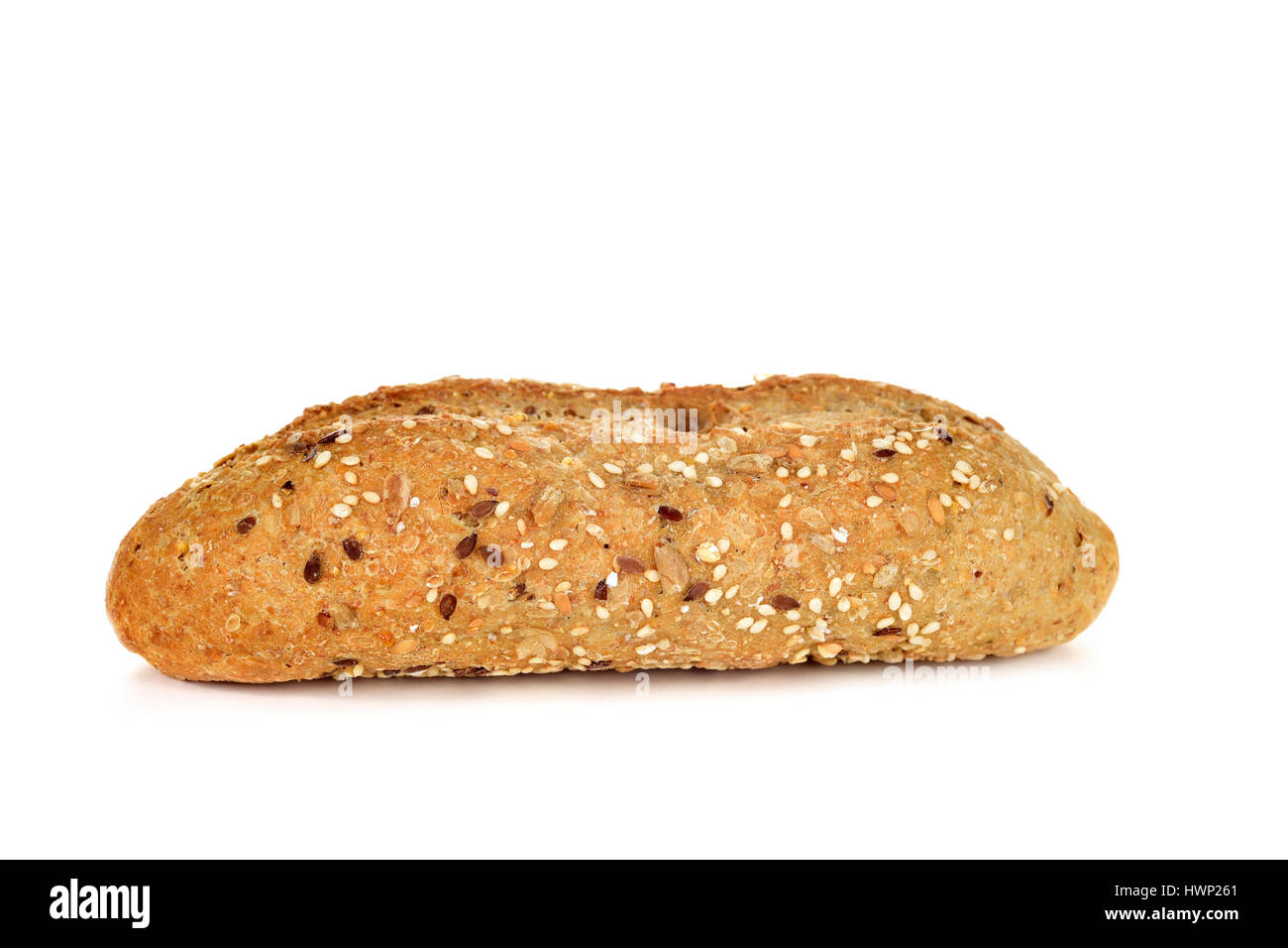 closeup of a wholemeal bread roll topped with different seeds, such as sesame and poppy seeds, on a white background - Stock Image