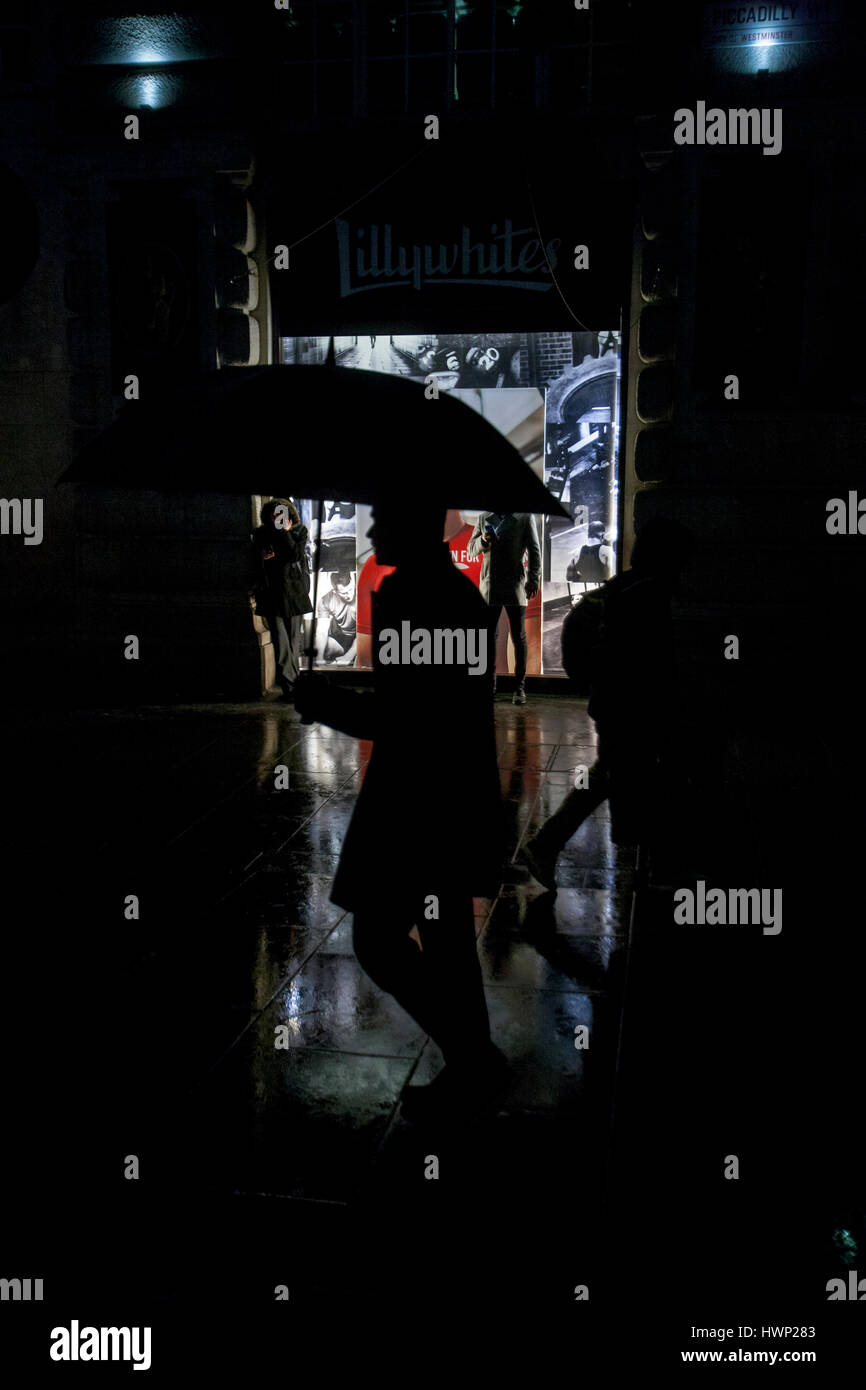 silhouetted man holding red umbrella passing lilywhites lit shop window at night in the rain - Stock Image