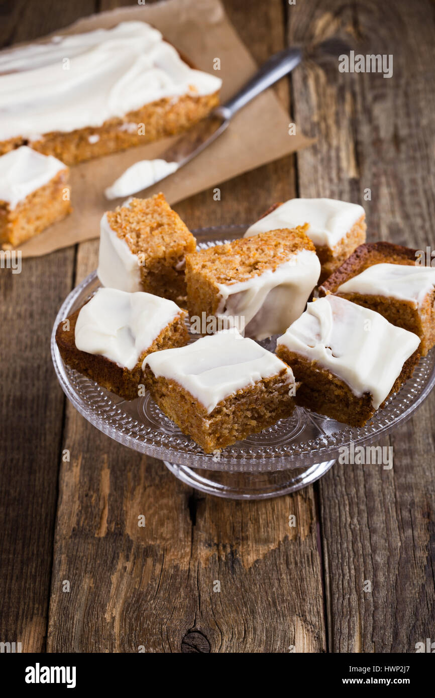 Homemade spiced pumpkin cake with cream cheese frosting sliced into squares, served on glass stand on rustic wooden - Stock Image