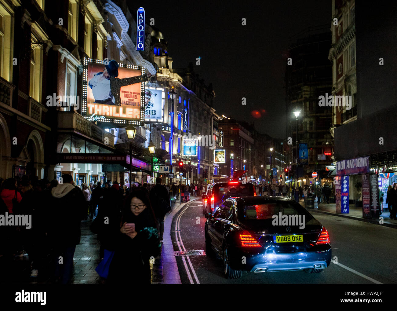 shaftesbury avenue theatre land west end London nighttime neon lights reflected in wet street - Stock Image