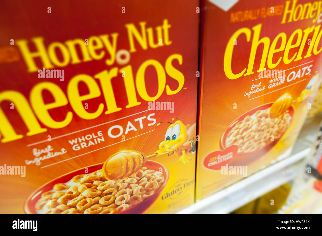 Boxes of General Mills Honey Nut Cheerios breakfast cereals featuring 'Buzz the Bee' in a supermarket in - Stock Image
