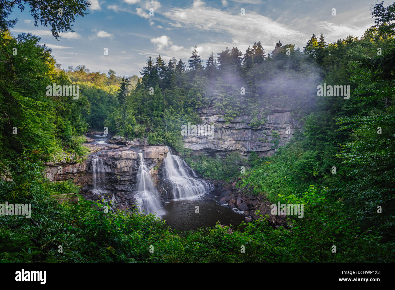Small pockets of fog sweep in and out, hanging over the iconic Blackwater Falls of West Virginia on an early summer - Stock Image