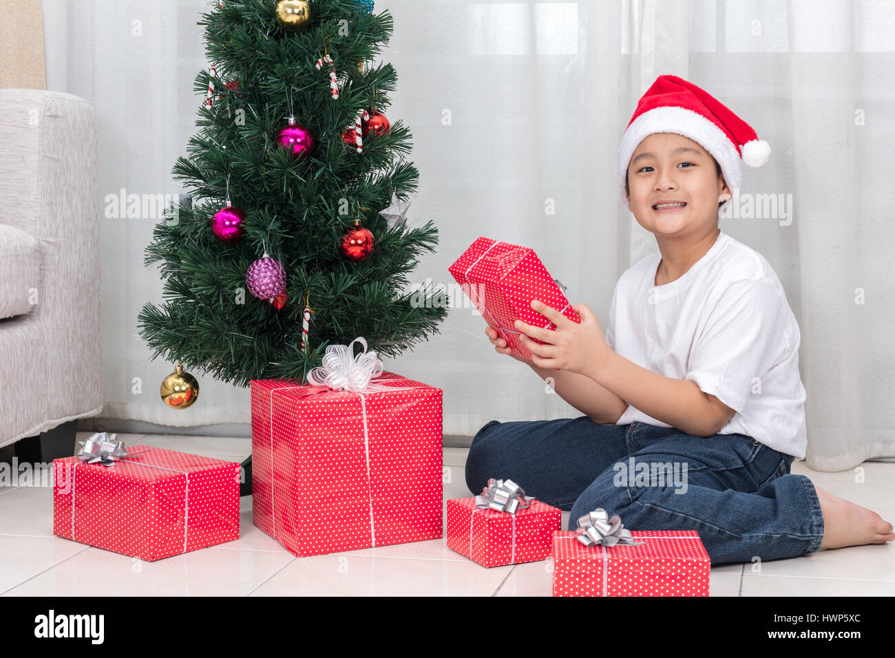 Asian Chinese little boy holding Christmas gift box in the living ...