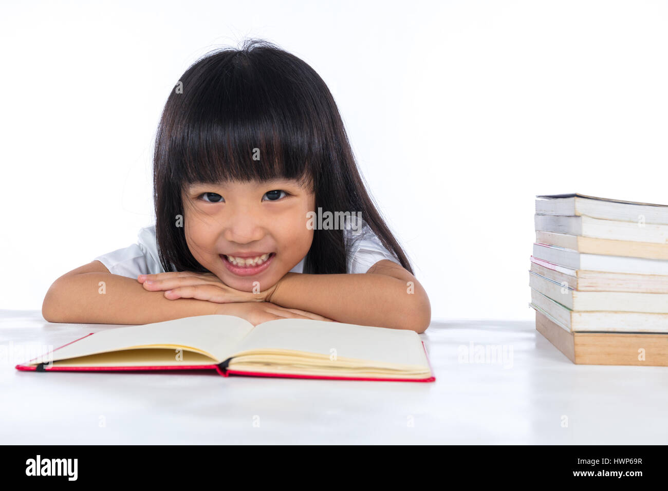 Smiling Asian Chinese little girl reading book in isolated white background. - Stock Image