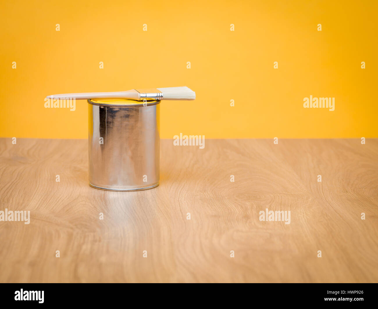 yellow paint container with brush on a wood table with freshly Stock ...