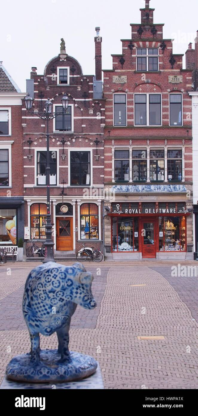 Delft, Netherlands - 2015, March 24: A Delft pottery cow looking towards a Royal Delftware pottery outlet across - Stock Image