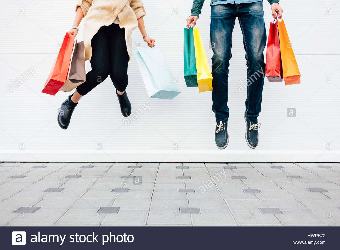 Closeup of woman and man jumping with shopping bags. Shopping concept with copy space. - Stock Image
